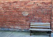 Empty bench and red brick wall