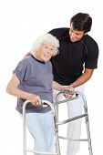 stock photo of zimmer frame  - Portrait of a happy senior woman holding walker while trainer assisting her over white background - JPG