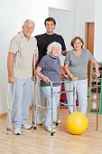 Full length happy portrait of disabled senior people with trainer