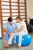 Young physical therapist examining senior woman's knee at hospital gym