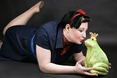 stock photo of rockabilly  - Rockabilly girl deeply in love with her frog shaped prince - JPG