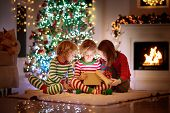 Children At Christmas Tree And Fireplace On Xmas Eve. Family With Kids Celebrating Christmas At Home poster