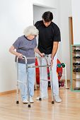 pic of zimmer frame  - Full length of a trainer assisting senior woman in moving walker - JPG