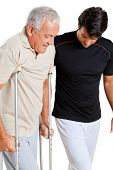 picture of crutch  - Trainer helping senior man with crutches to walk over white background - JPG