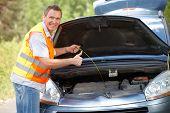 Hombre comprobación de nivel de aceite en una varilla de motor de coche y mostrando el signo ok