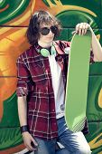 cool skater with his skateboard against a graffiti wall
