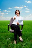 smiley businesswoman with documents showing thumbs up at the field