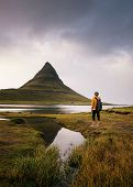 Young Hiker With A Backpack Looks At The Kirkjufell Mountain In Iceland. This 463 M High Mountain Is poster