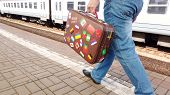A Man Is Walking Along A Railway Platform. Holding An Old Suitcase In His Hands. The Suitcase Is Dec poster