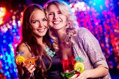 Cheerful girls dressed for party smiling at camera holding cocktails