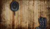Black Cowboy boots and hat against a weathered cedar background panel.