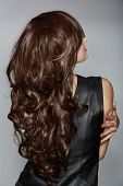 back of the woman with long brown curly hair with healthy shine, wearing a leather dress over a stud