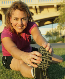 stock photo of workout-women  - Fit woman stretches before exercise outdoors in an urban setting - JPG