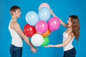 Young Boy Presenting Balloons To A Girl.