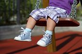 image of swings  - Feet of unrecognizable baby swinging on the playground alone - JPG