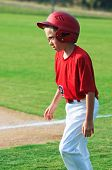 foto of little-league  - Little league youth baseball boy with helmet walking across ballpark - JPG