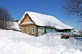 Wooden House And A Car In Snow Drifts
