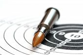 stock photo of murder  - single rifle bullet on paper target for shooting practice - JPG