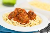 stock photo of meatball  - Spanish albondigas (meatballs) in tomato sauce on spaghetti served in bowl (Selective Focus Focus on the meatball in the front)