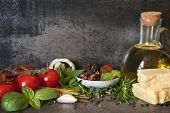 Italian food background, with vine tomatoes, basil, spaghetti, mushrooms, olives, parmesan, olive oi