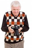 senior man reviewing pictures on SLR camera isolated on white