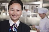 Restaurant hostess in industrial kitchen