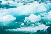 Detailed photo of the Icelandic glacier iceberg in a ice lagoon with incredibly vivid colors and a n