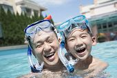 Portrait of father and son with snorkeling equipment in pool
