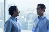 Two businessmen standing by window and talking in office