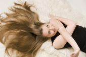 Girl Lies On A Fur Bedspread