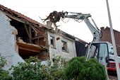 An old house is demolished with an excavator