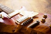 Red sunburst solid body electric guitar with well used leather strap.