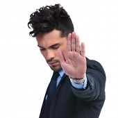 young business man making the stop hand sign on white background