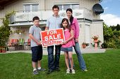 Young Family Holding A Foreclosure Sign