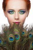 stock photo of female peacock  - Woman with colorful makeup and peacock feathers - JPG
