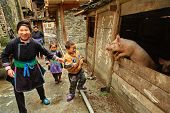 Family With Children Of Chinese Farmers, Stands Near The Pigsty.