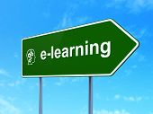 Education concept: E-learning and Head With Gears on road sign