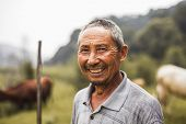 Portrait of smiling farmer with livestock in background