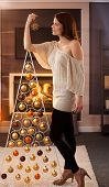 Christmas portrait of pretty woman standing by design tree with star handheld, smiling, daydreaming in cosy living room.