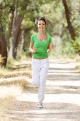 Young Woman Jogging In Green Forest