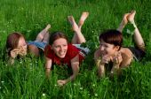 Laughing Girls Lay In A Green Summer Grass