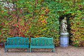 Two wooden benches on alley in front of bushes with lush colorful foliage and old sculpture in autumn Racconigi park, Italy.