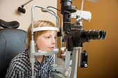 stock photo of slit  - Preadolescent boy undergoing eye examination with slit lamp in store - JPG