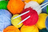 stock photo of coiled  - Colorful balls of wool yarn and knitting needles - JPG