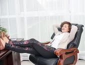 foto of peg-leg  - Female boss feet on their desks - JPG