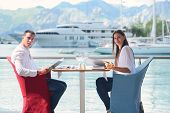 happy young couple having lanch at beautiful restaurant on by the sea on  beach