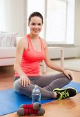 fitness, home and diet concept - smiling teenage girl with bottle of water and dumbbells after exerc
