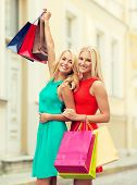 sale and tourism, happy people concept - beautiful women with shopping bags in the ctiy