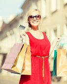 sale and tourism, happy people concept - beautiful blonde woman with shopping bags in the ctiy