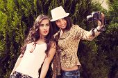 two young women take photo with camera outdoor shot
